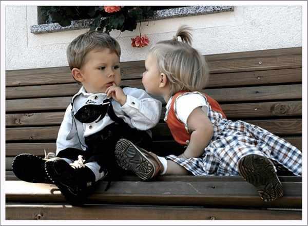 Девочка и мальчик сидят на скамейке