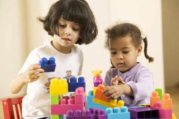 Две девочки разных национальностей играют в конструктор