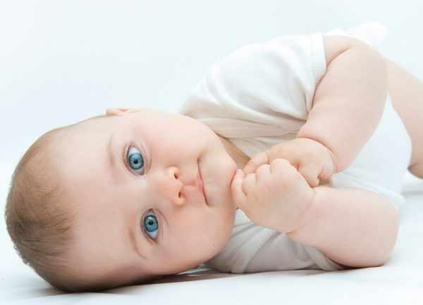 Малыш с голубыми глазами лежит на боку