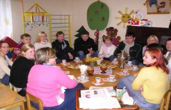 Воспитатель и родители сидят за накрытым к чаю столом