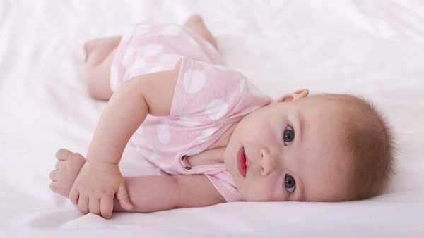 Ребёнок в розовом костюмчике лежит на кровати
