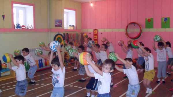 Группа детей выполняет упражнение с мячами