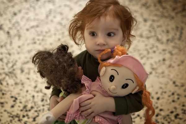 Девочка держит двух больших кукол