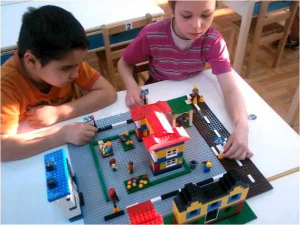 Мальчик и девочка играют с готовым макетом