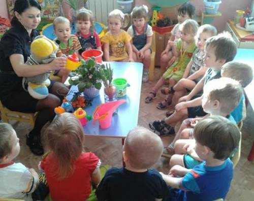 Воспитательница с мягкой игрушкой на руках что-то рассказывает сидящим полукругом детям