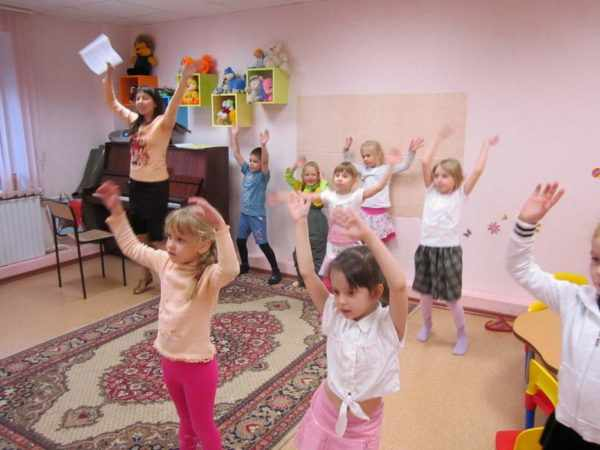 Дети и педагог танцуют, подняв руки вверх