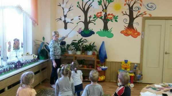 Воспитательница показывает на стену с макетами деревьев в разное время года, дети стоя слушают