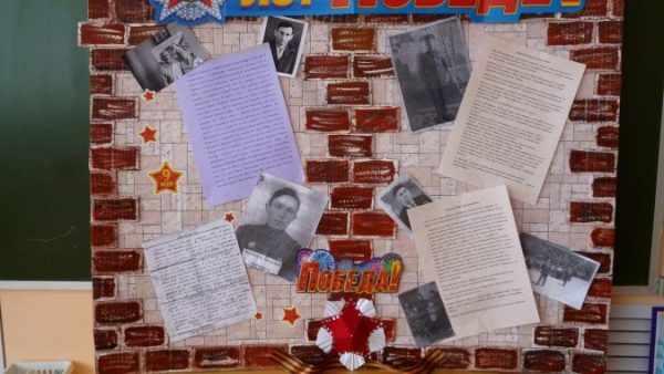 Стенд с кирпичиками с фотогорафиями земляков — героев войны и сведениями о них