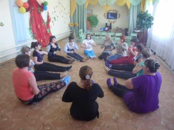 Родители сидят в кругу на ковре и выполняют дыхательное упражнение