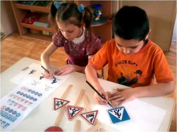 Мальчик и девочка изготавливают дорожные знаки из бумаги и деревянных палочек
