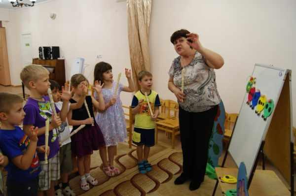 Дети и педагог на музыкальном занятии в ДОУ