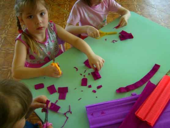 Дошкольники вырезают элементы цветов из гофрированной бумаги