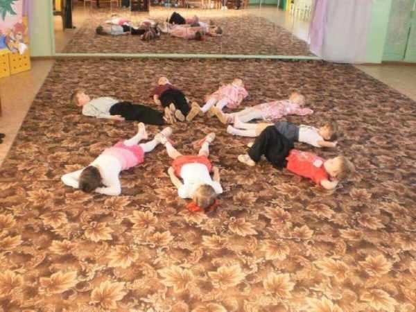Дети лежат на ковре в музыкальном зале