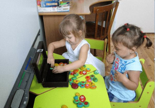 Две девочки играют с окрашенными камешками