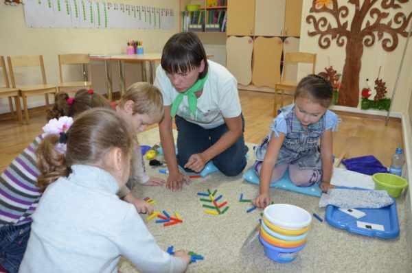 Дети и педагог играют со счётными палочками на ковре