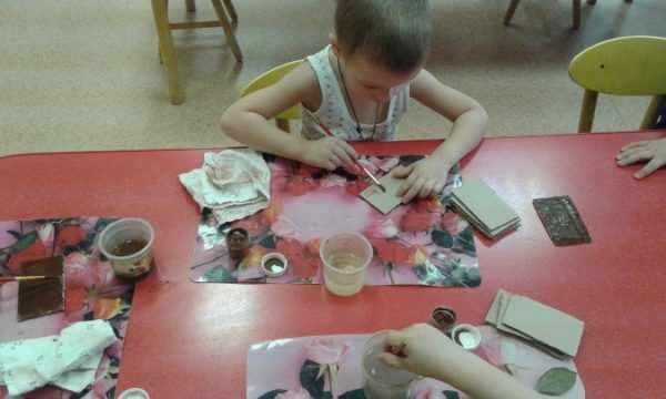 Ребёнок красит картонные кирпичики
