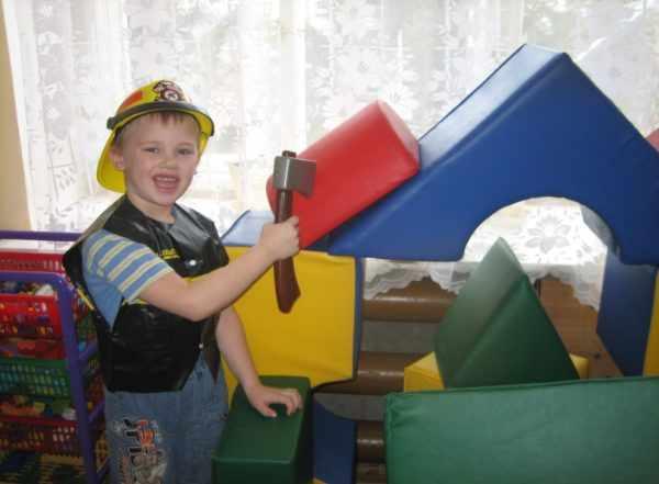 Мальчик в жёлтой каске играет в строителя