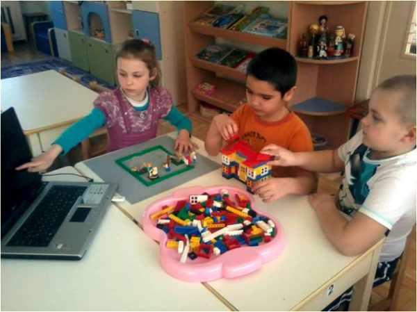 Трое детей собирают здание из конструктора