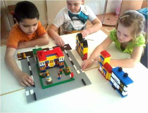 Дети конструируют перекрёсток на большой пластине
