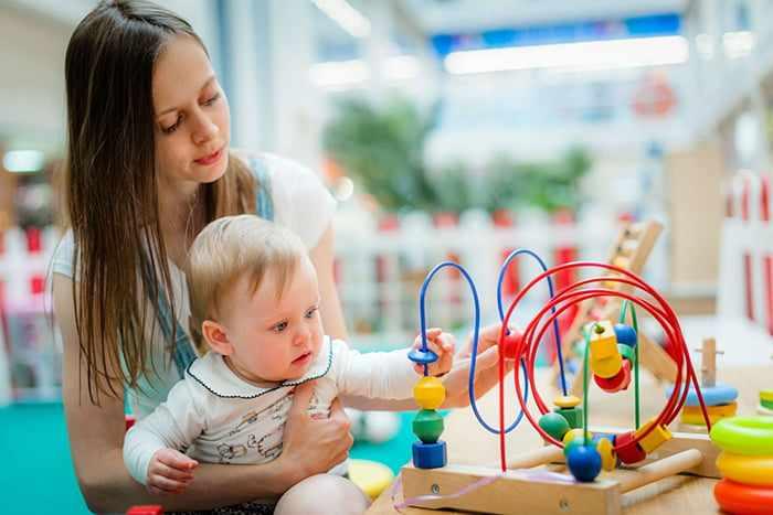 Мама с малышом рассматривают игрушку