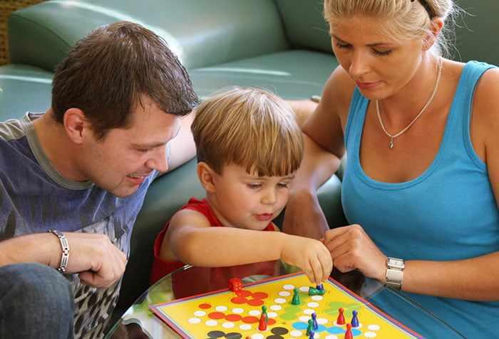 Родители играют с ребенком в настольную игру