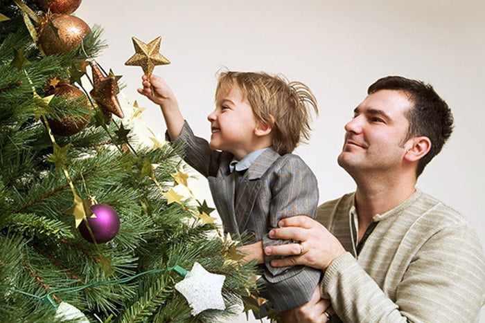 Ребенок с отцом украшает елку