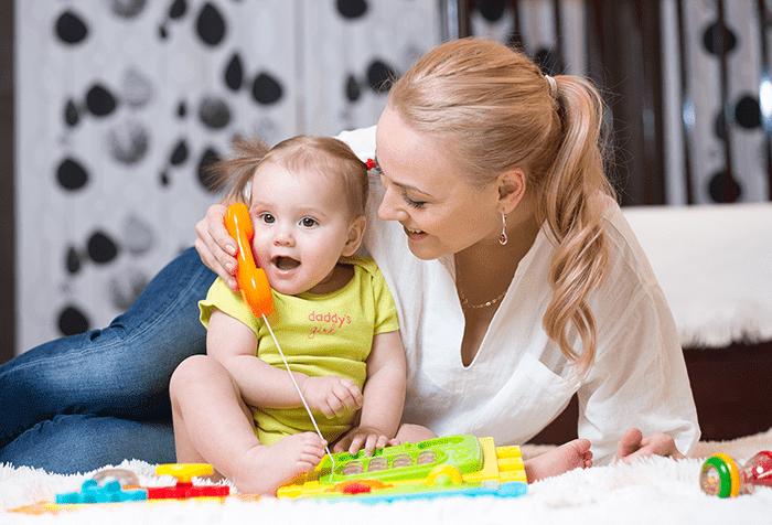 Маленькая девочка с мамой и игрушечным телефоном