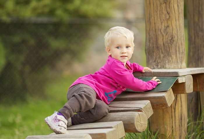 Маленький ребенок на деревянной лестнице в парке